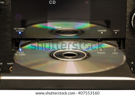 Selective focus cd and its reflection on the surface of a cd player - stock photo