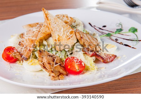 Selective focus Classical Caesar salad with roasted chiken, bacon, quail eggs, lettuce leaves, toasts, parmesan, cherry tomatoes and cream sause on the white round  plate close up on the served table - stock photo