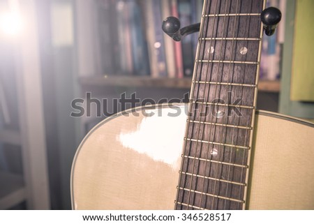 Selective focus close up acoustic guitar with book music background , Lens flare technician