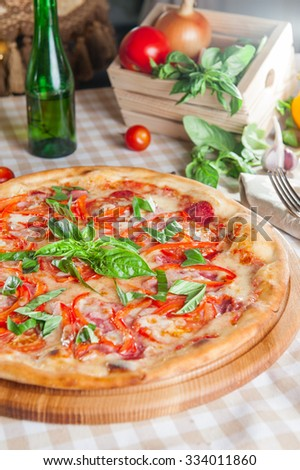 Selective focus Close up Delicious Meat Pizza with Salami, Bacon and Tomato Slices decorated with fresh basil on the wooden board on the served restaurant table with different colourful vegetables