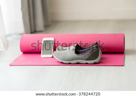 Selective focus close up gray sport shoes and smart phone on pink yoga mat at home, healthy concept. - stock photo
