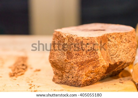 Selective focus close up view of large chocolate block on wooden cutting board with shavings and copy space - stock photo