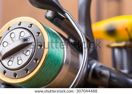 selective focus closeup fishing bait wobbler and reel with line on wooden background
