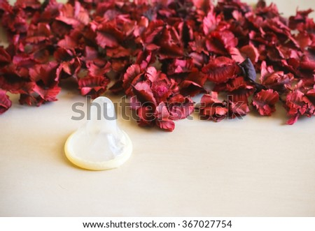 Selective focus condom and dry flower background. - stock photo