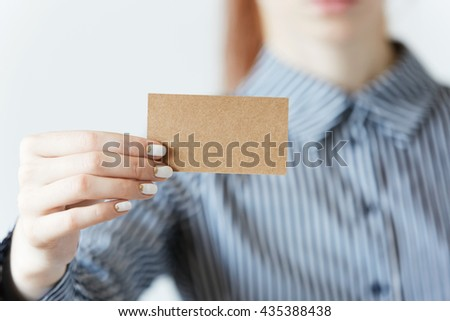 Selective focus. Cropped portrait of female entrepreneur or office worker in striped formal T-shirt and red hair holding a parchment business card with copy space for your text or advertising content - stock photo