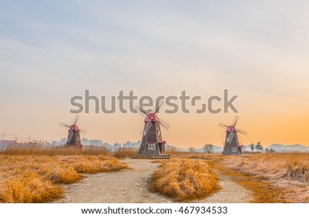 Selective focus Field of grass and blurred of traditional dutch old wooden windmill in vintage color