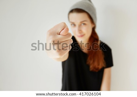 Selective focus, film effect. Close up of young stylish girl showing fig sign at the camera. Hipster female wearing gray cap and black T-shirt having fun making fig gesture posing isolated indoor.  - stock photo