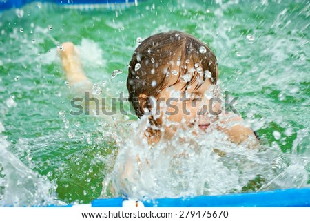 selective focus. funny little girl splashing in the water in swimming pool. child outdoors - stock photo