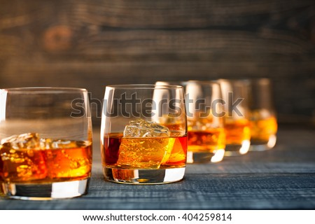 selective  focus glass of cold whiskey on wooden-table - stock photo
