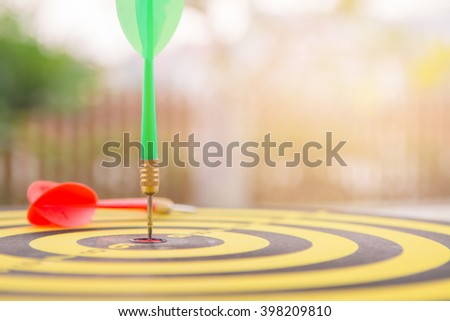 selective focus green dart hitting in target center of dartboard and falling red dart with orange lighting,competitive business concept,organization that has potential to be lead the business - stock photo