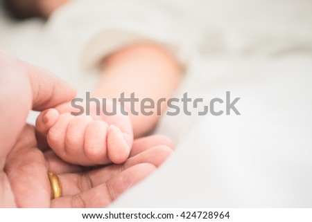 selective focus hand the sleeping baby in the hand of mother close-up