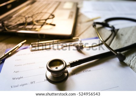 Selective focus Health care concept. Stethoscope on a medical chart with Eyeglasses on laptop with effect light added.