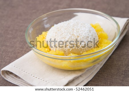 Selective focus image of a semolina pudding with mango and coco flakes.