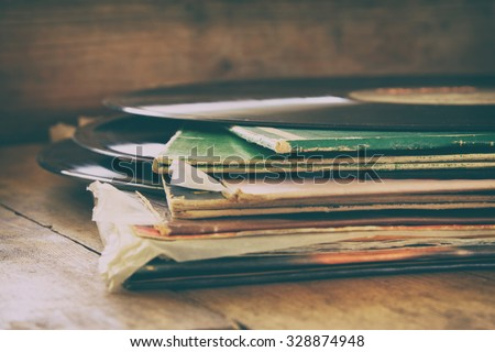 selective focus image of records stack with record on top over wooden table. vintage filtered  - stock photo
