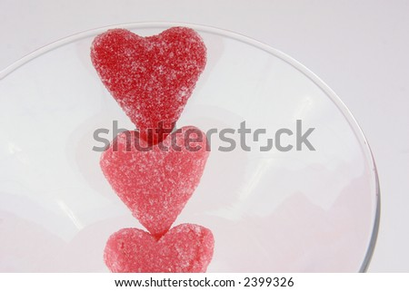 Selective focus image of three heart shaped candies in a glass.