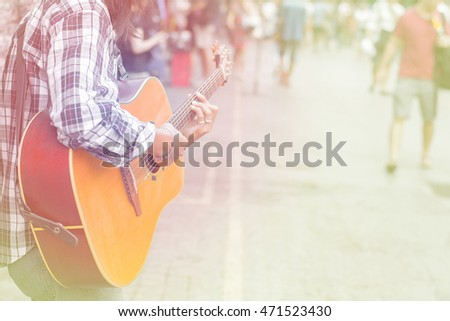 Selective focus man playing guitar on walking street, filter color effect. copy space .Concept music for  life.