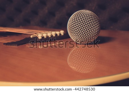 selective focus Microphone on classic guitar background.