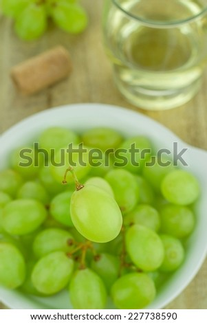 Selective focus of a single grape over a bowl of grapes - stock photo