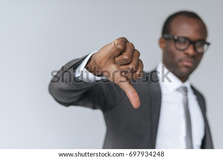 selective focus of african american businessman showing thumb down isolated on grey