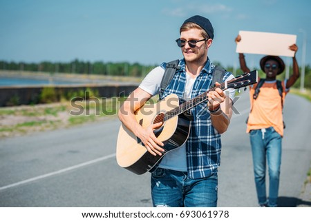 selective focus of caucasian man playing guitar while african american friend with empty cardboard hitchhiking behind