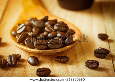 selective focus of coffee beans on wooden spoon ,vintage color tone. - stock photo