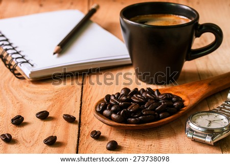 selective focus of coffee beans on wooden spoon with notebook and cup of espresso ,vintage color tone. - stock photo