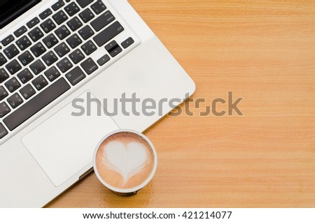 Selective focus of coffee latte art heart with blurred notebook (laptop) on workspace of wooden table. Concept for office workplace, freelance, coffee time, blogger, social, programmer, background