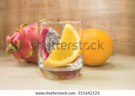 selective focus of fresh orange decorate with dragon fruit on wooden background, vintage color tone.