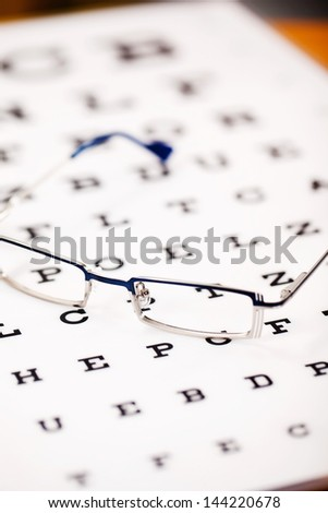 Selective focus of glasses on Snellen chart - stock photo