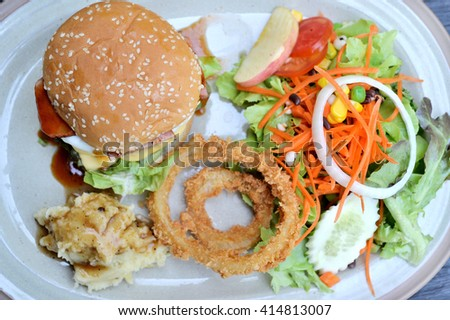 Selective focus of hamburger with ham and cheese, mash potato, deep fry onion ring and salad