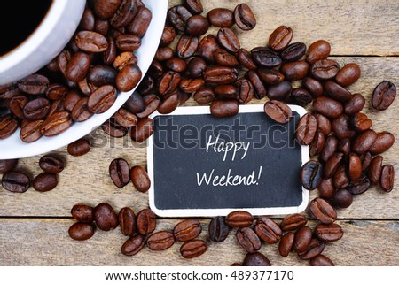 Selective focus of HAPPY WEEKEND! text written on the chalkboard, coffee beans and white cup on the wooden background.
