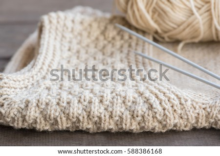 Selective focus of knitted sweater with knitting needles and yarn on wooden background.