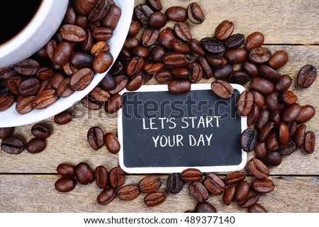 Selective focus of LET'S START YOUR DAY text written on the chalkboard, coffee beans and white cup on the wooden background.