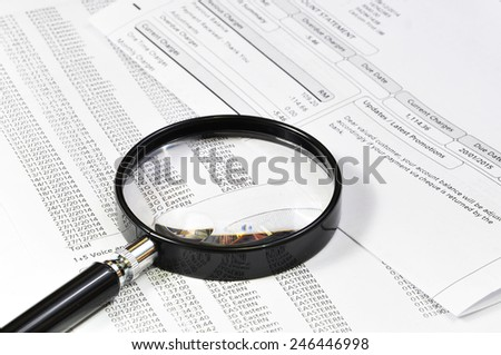 Selective focus of magnifying glass examining bill statement - stock photo