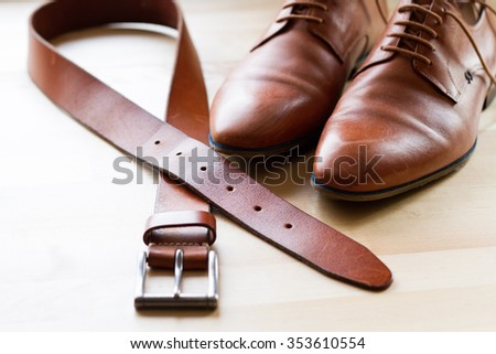 Selective focus of  men's leather belt and shoe on wooden table - stock photo