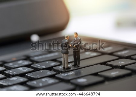 Selective focus of miniature businessman handshake about business investment on the keyboard background as Technology, Commitment and Agreement concept.