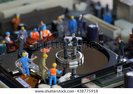 Selective focus of miniature businessman handshake and worker commitment to repair harddisk and fixed problem harddisk (hard disk) of Personal computer (PC) as commitment and industrial concept. - stock photo