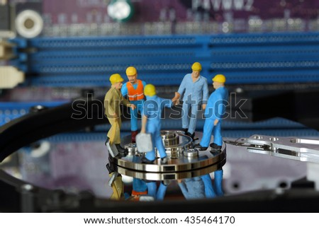 Selective focus of miniature engineer and worker discuss in job about repair harddisk (hard disk) and fixed problem harddisk (hard disk) of Personal computer (PC) as business and industrial concept. - stock photo