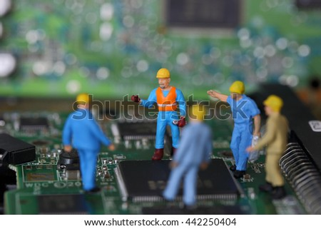 Selective focus of miniature engineer and worker discuss to fixed problem or repair on chips in computer mainboard as business and industrial concept. - stock photo