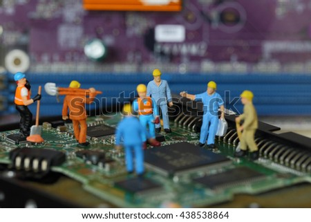 Selective focus of miniature engineer and worker fixed problem and repair chipset of Personal computer (PC) on blurred mainboard background as business and industrial concept. - stock photo