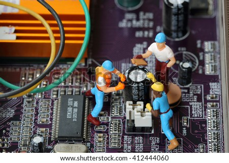 Selective focus of miniature engineer and worker fixed problem mainboard computer and use for business background. - stock photo