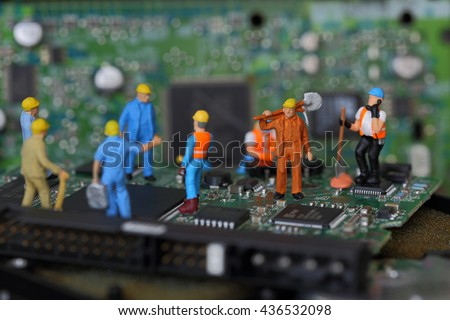 Selective focus of miniature engineer and worker fixed problem on chips and computer mainboard as business and industrial concept. - stock photo