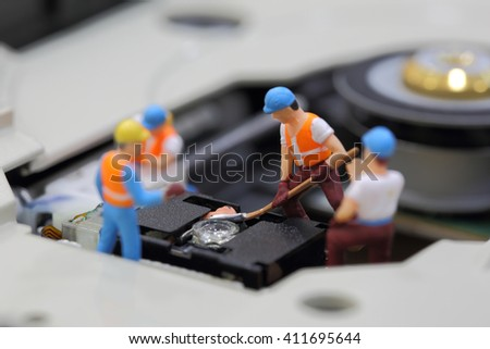 Selective focus of miniature engineer and worker fixed to clean CD rom reader of mainboard computer and use for business background. - stock photo