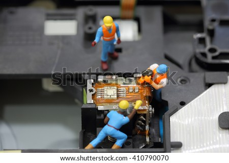 Selective focus of miniature engineer and worker fixed to remove screw for repair cd rom of computer and use for business background. - stock photo