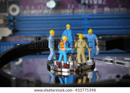Selective focus of miniature engineer and worker meeting and discuss harddisk (hard disk) and fixed problem harddisk (hard disk) of Personal computer (PC) as business and industrial concept. - stock photo