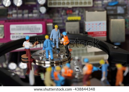 Selective focus of miniature engineer and worker meeting and maintenance hard disk of Personal computer (PC) on blurred mainboard background as business and industrial concept. - stock photo