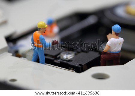 Selective focus of miniature engineer and worker meeting and talk about clean CD rom reader of mainboard  computer and use for business background. - stock photo
