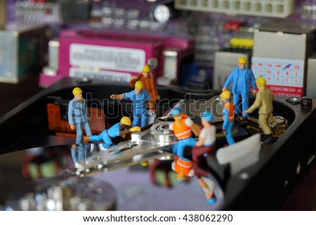Selective focus of miniature engineer and worker repair harddisk (hard disk) and fixed problem harddisk (hard disk) of Personal computer (PC) as technology and industrial concept. - stock photo