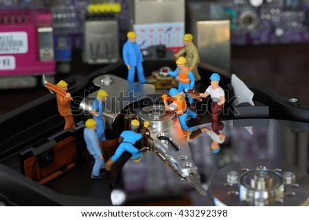 Selective focus of miniature engineer and worker repair harddisk (hard disk) or fixed problem hard disk of Personal computer (PC) as business and industrial concept. - stock photo