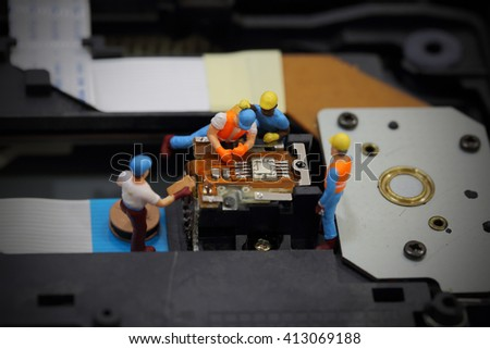 Selective focus of miniature engineer and worker to fixed and repair cd rom of mainboard computer and use for business background. - stock photo